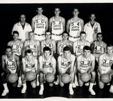 Roger Schaffer poses with the USD Men's Basketball Team during the 1963-1964 season.